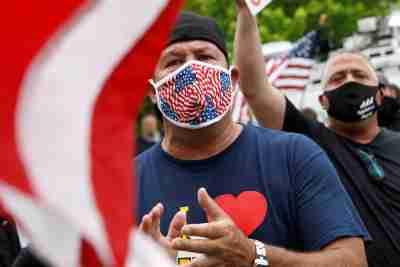 Les partisans de Bobby Catone, propriétaire d'un salon de bronzage Sunbelievable, tiennent des drapeaux et des pancartes après avoir ouvert son entreprise contre les recommandations locales en matière de santé et un ordre de fermeture pendant l'éclosion de la maladie à coronavirus (COVID-19), dans le quartier de Staten Island à New York, États-Unis, 28 mai 2020. REUTERS / Brendan McDermid