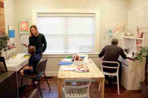 """Helen and Tyler McClenahan help their kids with school work at home during Washington Governor's """"stay home, stay healthy"""" initiative as efforts continue to help slow the spread of coronavirus disease (COVID-19) in Seattle, Washington, U.S. March 27, 2020.  REUTERS/Jason Redmond"""