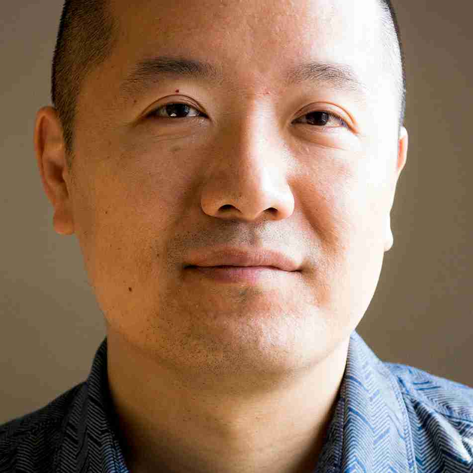 An Asian American man with closely shaved head wearing a blue, patterned collared shirt looks at the camera with a slight smile