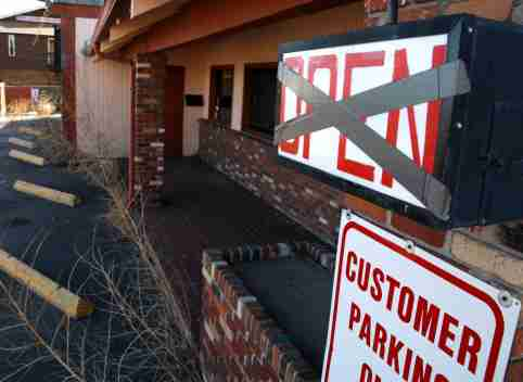 Weeds are seen near a sign hanging outside a bar that went out of business in Denver February 26, 2009.  REUTERS/Rick Wilking (UNITED STATES)