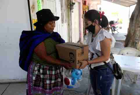 """An employee of the clothing brand """"El Chapo 701"""", owned by Alejandrina Gisselle Guzman, daughter of the convicted drug kingpin Joaquin """"El Chapo"""" Guzman, hands out a box with food, face masks and hand sanitizer to an elderly woman as part of a campaign to help cash-strapped elderly people during the coronavirus disease (COVID-19) outbreak, in Guadalajara, Mexico April 16, 2020. The number 701 refers to the 2009 World's Billionaires ranking given by Forbes magazine to Mexican drug lord Joaquin """"El Chapo"""" Guzman. REUTERS/Fernando Carranza"""