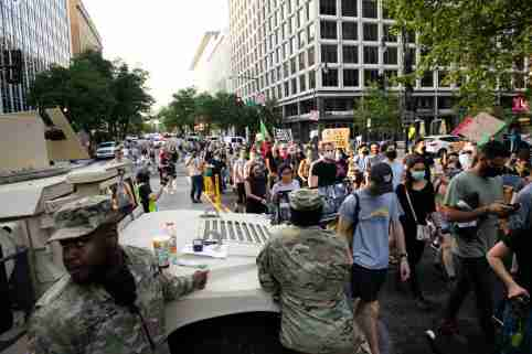Protesters with Sanctuary DMV march by members of the US Armed Forces and an armored vehicle in downtown Washington, D.C., on June 19, 2020 amid the Coronavirus pandemic. After weeks of anti-racist and Black Lives Matter demonstrations in America and beyond, thousands of protesters again gathered in Washington on Juneteenth, commemorating the day the final slaves were freed in 1865 and marching throughout the capital. (Graeme Sloan/Sipa USA)No Use UK. No Use Germany.