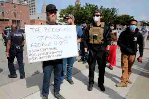 "Armed men, one carrying a ""The Boogaloo stands with George Floyd"" sign, are seen as protesters rally against the death in Minneapolis police custody of George Floyd, in Detroit, Michigan, U.S. May 30, 2020. Picture taken May 30, 2020.   REUTERS/Rebecca Cook"