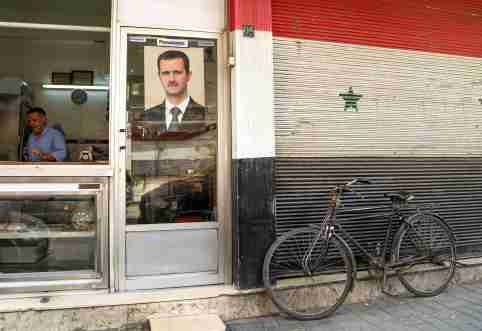 FILE PHOTO: A picture of Syrian President Bashar al-Assad is seen on a door of a butcher shop, during a lockdown to prevent the spread of the coronavirus disease (COVID-19), in Damascus, Syria April 22, 2020. Picture taken April 22, 2020. REUTERS/Yamam Al Shaar/File Photo
