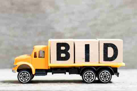 Truck hold letter block in word bid on wood background