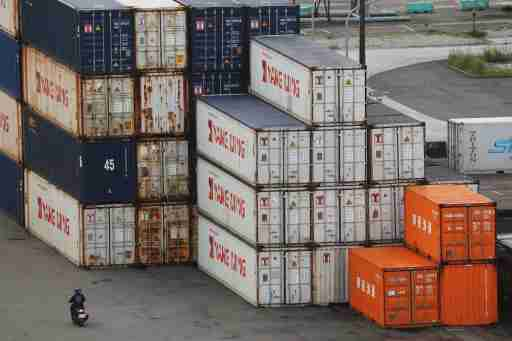 A person drives a motorcycle by shipping containers at a port in Keelung, Taiwan, June 10, 2020. REUTERS/Ann Wang