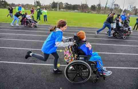 Competitors in wheelchairs get some assistance around the track during the Developmental Adapted Physical Education track meet Friday, May 10, at Apollo High School. Students from St. Cloud junior and high schools, Sartell, Sauk Rapids and Foley students took part in the area event, the first of its kind at Apollo.Poy 27