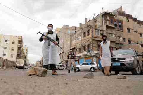 Security men wearing protective masks stand on a street during a 24-hour curfew amid concerns about the spread of the coronavirus disease (COVID-19), in Sanaa, Yemen May 6, 2020. REUTERS/Khaled Abdullah     TPX IMAGES OF THE DAY