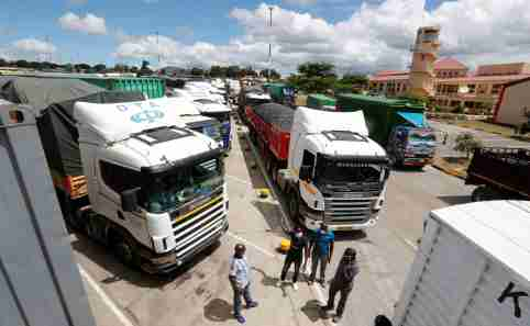 Truck drivers wait near their parked vehicles for the coronavirus disease (COVID-19) test results at the Namanga one stop border crossing point between Kenya and Tanzania, in Namanga, Kenya May 12, 2020. REUTERS/Thomas Mukoya