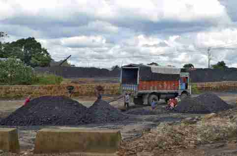 "Labourers work at a coal stockyard in East Jaintia Hills in Meghalaya, India, September 16, 2015. A senior Indian politician has been lobbying New Delhi to lift a ban on dangerous, small-scale coal mining operations in his state, without disclosing that his wife owns several mines there, according to documents seen by Reuters. So-called ""rat-hole"" mining practised in Meghalaya state killed thousands of workers, including children, before the ban was imposed in April last year. At its peak the state produced coal worth $4 billion a year, or about a tenth of India's total production, nearly all from this form of small-scale mining. Picture taken September 16, 2015. REUTERS/Krishna N. Das"