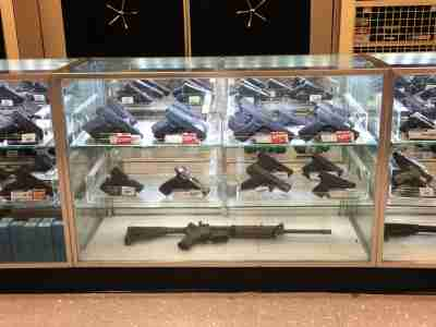 Display case filled with different types of guns for sale.