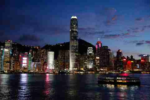 FILE PHOTO: A Star Ferry boat crosses Victoria Harbour in front of a skyline of buildings during sunset in Hong Kong, China June 29, 2020. REUTERS/Tyrone Siu/File Photo