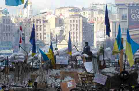 A pro-European integration protester looks out from a barricade on Independence Square in Kiev on December 14, 2013.
