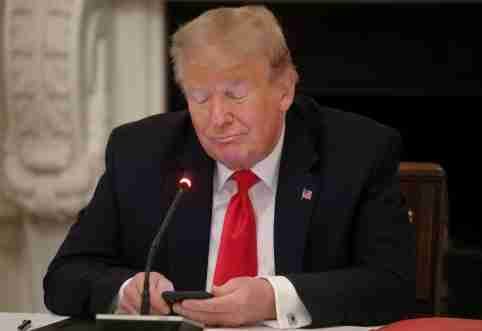 U.S. President Donald Trump is using a mobile phone during a roundtable discussion on the reopening of small businesses in the State Dining Room at the White House in Washington, U.S., June 18, 2020.