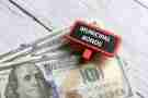 Selective focus of dollar notes and red tag written with MUNICIPAL BONDS on white wooden background.