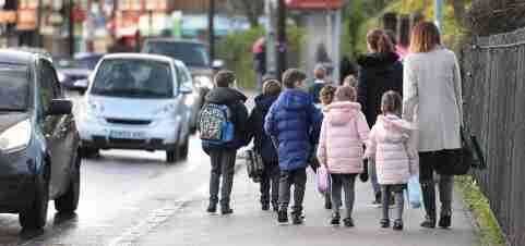 Parents walk their children to school in Hornchurch, Essex, past stationary vehicles near to the school grounds. PA Photo. Picture date: Friday January 17, 2020. Photo credit should read: Nick Ansell/PA Wire