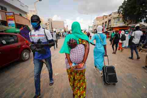 A woman carries her protective mask in her hands as hundreds of thousands of the Senegalese Mouride Brotherhood pilgrims gather for the annual Grand Magal festival, as the global spread of the coronavirus disease (COVID-19) continues, in the holy city of Touba, Senegal October 5, 2020. Picture taken October 5, 2020. REUTERS/Zohra Bensemra