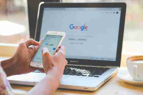 A woman is typing on Google search engine from a laptop and iPhone. Editorial credit: PK Studio / Shutterstock.com