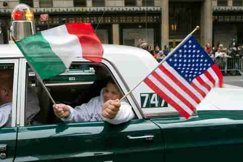 A participant waves American and Italian flags from the back of an antique police car during the annual Columbus Day Parade along Fifth Avenue in New York October 8, 2012.  REUTERS/Keith Bedford (UNITED STATES - Tags: SOCIETY)