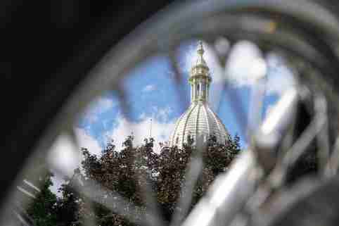 The Michigan State Capitol building is seen through the spokes of a motorcycle during the ABATE of Michigan Annual Freedom Rally outside of the Michigan State Capitol building in Lansing on Sept. 29, 2020. Bikers gathered to speak on behalf of motorcyclists who want changes to the recent auto insurance reform law that puts motorcyclists at a disadvantage.