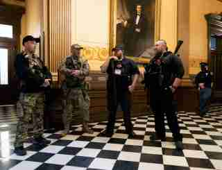 FILE PHOTO: Members of a militia group, including Michael John Null and Willam Grant Null (R) who were charged October 8, 2020 for their involvement in a plot to kidnap the Michigan governor, attack the state capitol building and incite violence, stand near the doors to the chamber in the capitol building before the vote on the extension of Governor Gretchen Whitmer's emergency declaration/stay-at-home order due to the coronavirus disease (COVID-19) outbreak, in Lansing, Michigan, U.S. April 30, 2020.  REUTERS/Seth Herald/File Photo