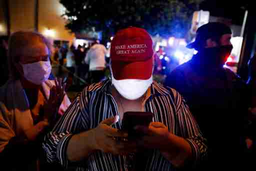 FILE PHOTO: A supporter of U.S. President Donald Trump wears a 'Make America Great Again' cap during the 2020 U.S. presidential election, in Miami, Florida, U.S., November 4, 2020. REUTERS/Marco Bello/File Photo