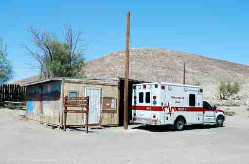 Ambulance in front of a small building.
