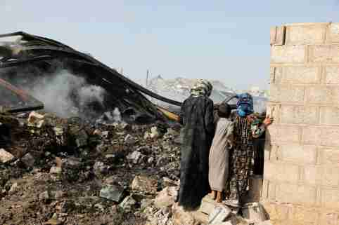 Children look at wreckage of a vehicle oil and tires store hit by Saudi-led air strikes in Sanaa, Yemen July 2, 2020. REUTERS/Khaled Abdullah