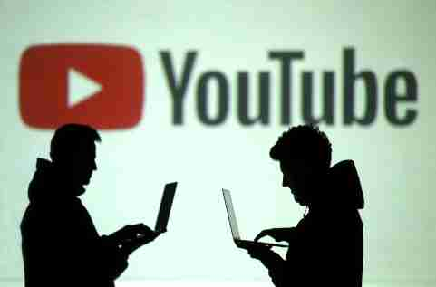 Silhouettes of mobile device users are seen next to a screen projection of YouTube's logo.