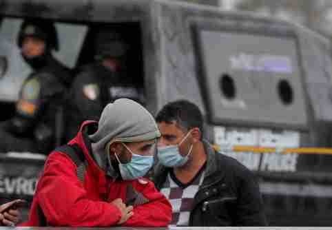 Men wearing protective face masks amid the coronavirus disease (COVID-19) pandemic walk beside police officer on Qasr el-Nil bridge leading to Cairo's Tahrir Square, Egypt December 17, 2020. REUTERS/Amr Abdallah Dalsh