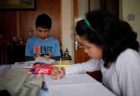 Sebastian Berrios and her sister Maria Fernanda study at home using electronic devices, as the country is under a nationwide quarantine to contain the coronovirus disease (COVID-19), in La Paz, Bolivia April 1, 2020. REUTERS/David Mercado