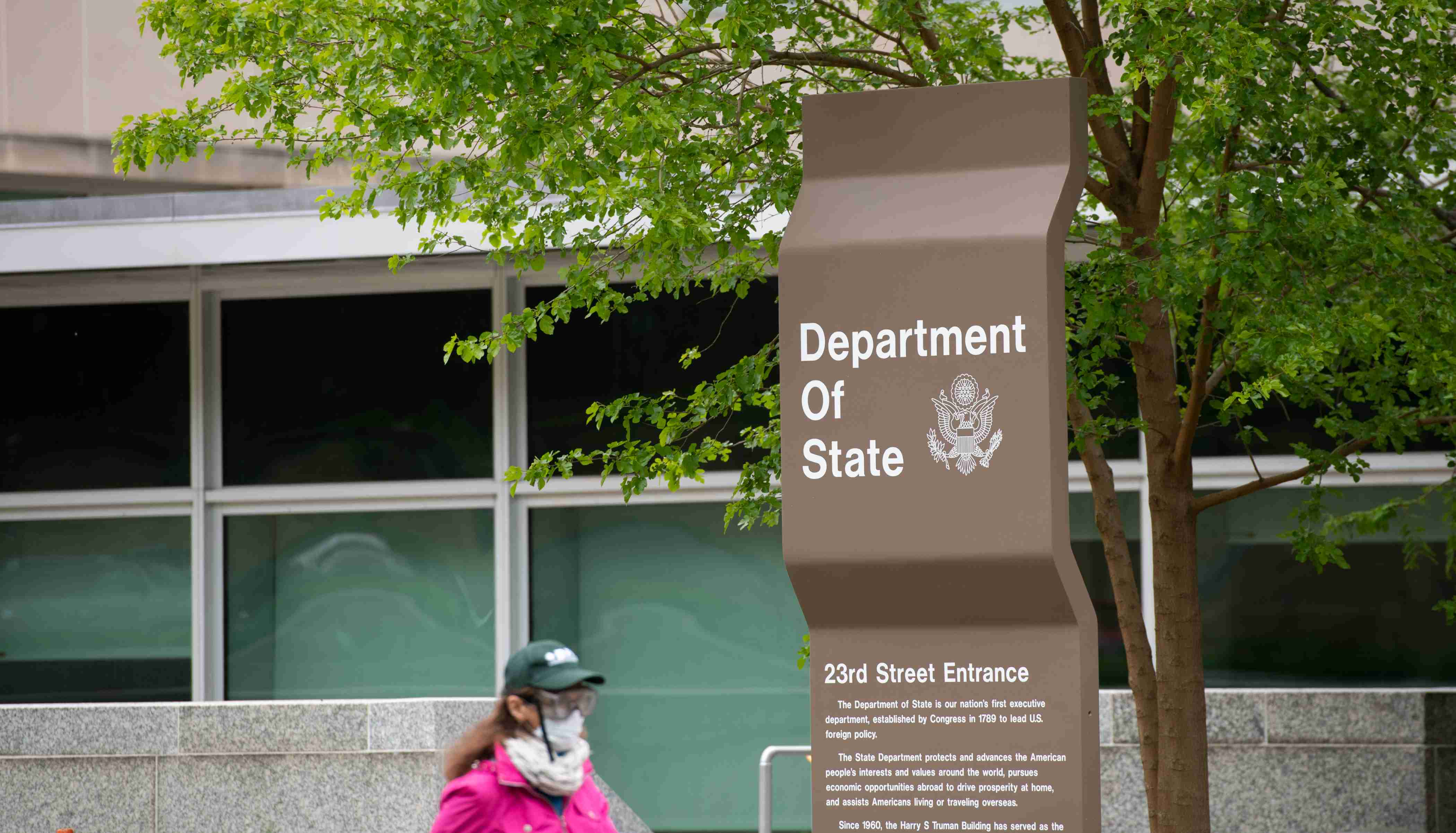 A pedestrian wearing gloves, goggles and a mask walks by the State Department in Washington, D.C. on April 23, 2020 amid the Coronavirus pandemic. After extended negotiations over an additional $500 billion in stimulus funding in response to the ongoing COVID-19 outbreak, the U.S. Congress is set send another economic relief bill to President Trump to sign into law after a House vote later today. (Graeme Sloan/Sipa USA)No Use UK. No Use Germany.