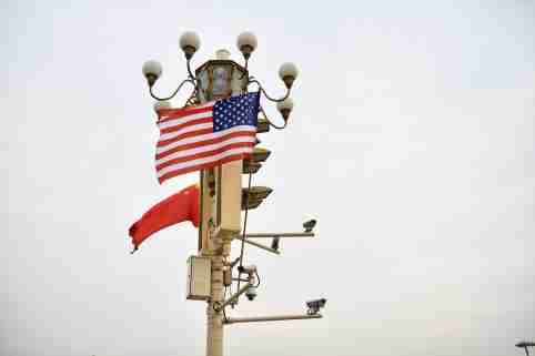 Chinese and American national flags flutter on a lamppost in Beijing festooned with surveillance cameras.