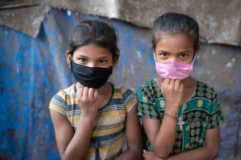 Two girls wear masks.
