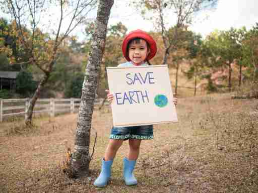 """Young girl holding a """"save earth"""" sign"""