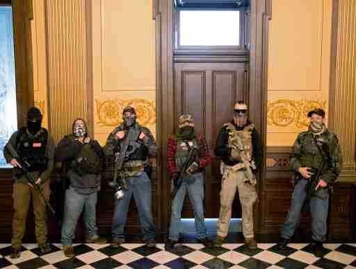 """FILE PHOTO: A militia group with no political affiliation from Michigan, including Joseph Morrison (3rd R), Paul Bellar (2nd R) and Pete Musico (R) who were charged for their involvement in a plot to kidnap Michigan Governor Gretchen Whitmer, attack the state capitol building and incite violence, stand in front of the governor's office after protesters occupied the state capitol building during a vote to approve the extension of Whitmer's emergency declaration/stay-at-home order due to the coronavirus disease (COVID-19) outbreak, in Lansing, Michigan, U.S. April 30, 2020. REUTERS/Seth Herald/File Photo   SEARCH """"AMERICA IN THE AGE OF TRUMP"""" FOR THE PHOTOS."""