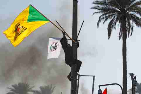 A member of Hashd al-Shaabi (paramilitary forces) holds a flag of Kataib Hezbollah militia group during a protest to condemn air strikes on their bases, in Baghdad, Iraq December 31, 2019. REUTERS/Khalid al-Mousily