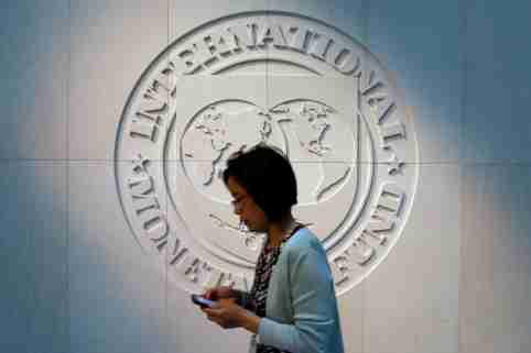 A woman walks past the International Monetary Fund (IMF) logo at its headquarters in Washington, U.S.