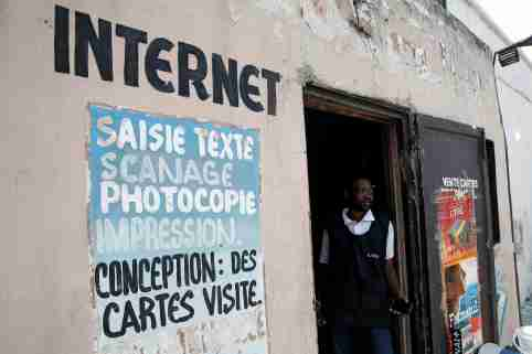 The owner of an internet cafe in Congo stands at the door of his business.