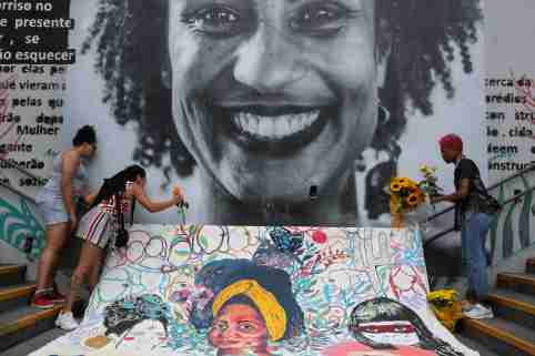 Women lay flowers at a mural of the murdered human rights activist Marielle Franco.