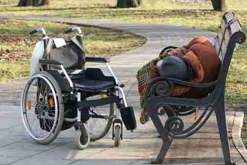Person sleeping on a bench outside next to a wheelchair
