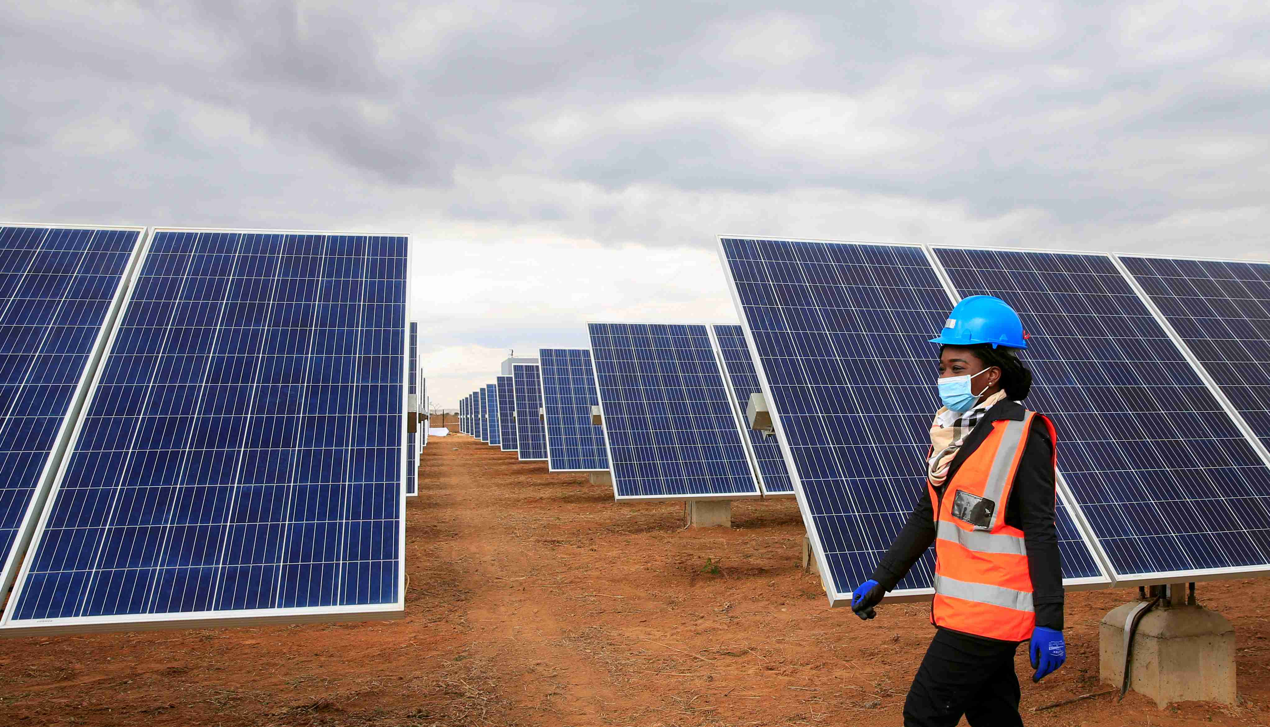 A worker walks past solar panels at Centragrid power plant in Nyabira, Zimbabwe, June 22, 2020. Picture taken June 22, 2020. REUTERS/Philimon Bulawayo