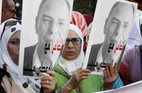 """Moroccan protesters hold up posters of Maati Monjib, a Moroccan professor of political history, to support him during a demonstration in the capital, Rabat, October 21, 2015. Monjib started a second hunger strike last Wednesday after authorities banned him from boarding a plane to Norway for an international conference on journalism in Lillehammer. The sign reads, """"Even if you use repression, your intimidation is useless"""". REUTERS/Stringer"""