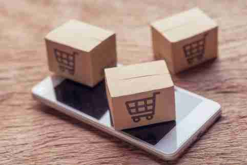 Online shopping - Paper cartons or parcel with a shopping cart logo and smartphone on wood table top