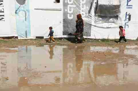 Syrian refugees walk near tents at an informal tented settlement in the Bekaa valley, Lebanon March 12, 2021. Picture taken March 12, 2021. REUTERS/Mohamed Azakir