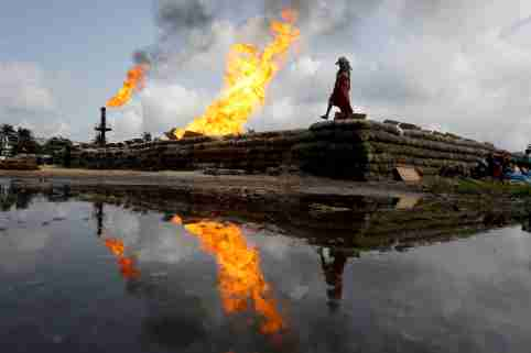Two gas flaring furnaces and a woman walking on sand barriers are reflected in a pool of oil-smeared water at a flow station in Ughelli, Delta State, Nigeria September 17, 2020. Picture taken September 17, 2020. REUTERS/Afolabi Sotunde     TPX IMAGES OF THE DAY