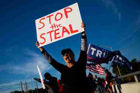"""A protester holds a sign reading """"stop the steal"""" at a pro-Trump protest."""