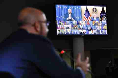 U.S. President Joe Biden and President of the European Council Charles Michel are seen on a large television screen attending a virtual summit.
