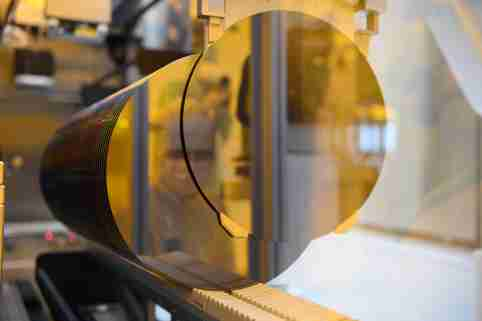 a workerin a semiconductor factory is refelected in a 300-milimeter wafer.