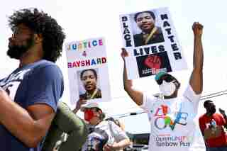 People attend a rally for racial justice on the one year anniversary of the police shooting of Rayshard Brooks, in Atlanta, Georgia, U.S., June 12, 2021.  REUTERS/Dustin Chambers     TPX IMAGES OF THE DAY